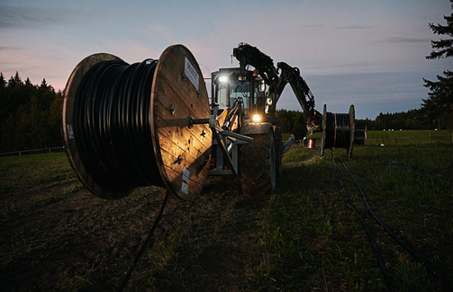 Tractor in the sunset holding a medium voltage cable drum